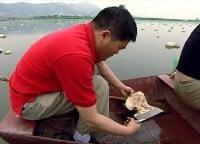 M. He, Propriétaire d'une des plus importantes ferme perlière de la région, ouvre une moule d'eau douce